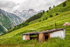 Poor old dilapidated house of  shepherd on green meadow. Poor old dilapidated abandoned house of the shepherd on a green meadow in the valley of the mountains Stock Photos