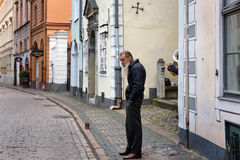 Poor old man at central street of old town in Riga, Latvia. RIGA, LATVIA - OCTOBER 2016: Poor old man at central street of old town in Riga, Latvia stock photo