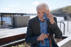 Poor old man crying outdoors. Do not offend the elderly people. Old sad neat man rubbing his tears away while sitting on the bench and remembering his wife stock images