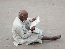 A poor old man reading a newspaper Royalty Free Stock Photo