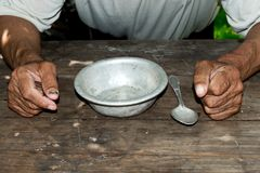 Poor old man`s hands and empty bowl on wooden background.An angry hungry man clenches his hands into fists. Royalty Free Stock Image