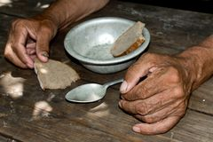 The poor old man`s hands hold an empty bowl. The concept of hunger or poverty. Selective focus. Poverty in retirement.Homeless. Al royalty free stock image