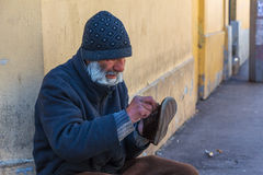 Poor old man shining shoes in the street Stock Photography