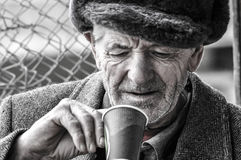 Poor old man. A very poor and old man looking at his empty glass royalty free stock photo