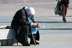 Poor old woman. Begging on the city street Stock Photo