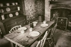 Poor peasants interior from 19th century, dining room with set wooden table and fireplace, sepia style photography stock image