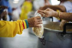 Poor people bring containers to contain food from the sharing of the rich.  royalty free stock image