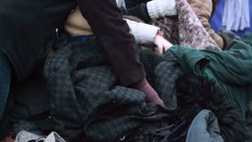 Poor people choosing second hand clothes winter outdoors. Stock footage stock footage