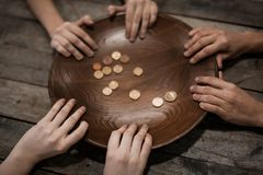 Poor people holding plate with coins. On wooden background Royalty Free Stock Images