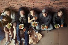 Poor people with plates of food sitting at wall indoors. View from above royalty free stock image
