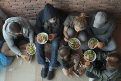 Poor people with plates of food sitting at wall indoors. View from above stock photography