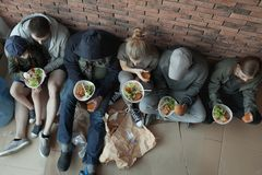 Poor people with plates of food sitting at wall indoors. View from above royalty free stock images