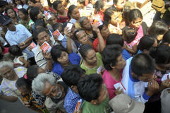 Poor people. Queued to redeem coupons to get cheap food in Solo, Central Java, Indonesia Royalty Free Stock Photo