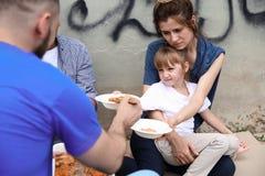 Poor people receiving food from volunteer. Outdoors royalty free stock photo