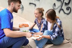 Poor people receiving food from volunteer Royalty Free Stock Photography