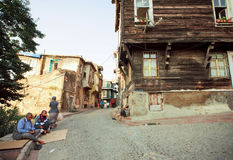 Poor people sitting on the cobbled street with old wooden buildings of turkish capital Royalty Free Stock Photos