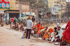 Poor people waiting for charity distributing food on the dirty streets of indian city. VARANASI, INDIA - JANUARY 2: Poor people waiting for charity distributing Stock Image