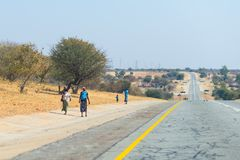 Poor people walking on the roadside in the rural Caprivi Strip, the most populated region in Namibia, Africa. Poor people walking on the roadside in the rural royalty free stock photography