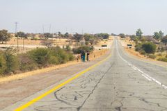 Poor people walking on the roadside in the rural Caprivi Strip, the most populated region in Namibia, Africa. Poor people walking on the roadside in the rural stock images