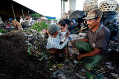 Poor people working in a scavenging at the dump Stock Photo