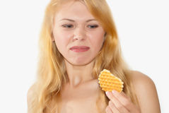 Poor-quality product. Girl shows discontent with quality of a waffle Stock Images