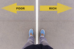 Poor or rich choice, text on asphalt ground, feet and shoes on f. Poor or rich choice; text on asphalt ground, feet and shoes on floor, personal perspective stock image
