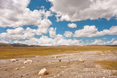 Poor road on a plateau under the big white clouds Royalty Free Stock Photography