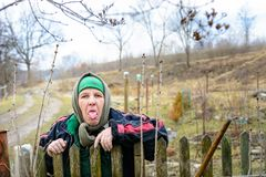 The poor rural grandmother shows the tongue near her fence, showing malice to everyone else royalty free stock image