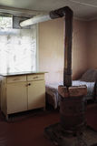 Poor rural room. The interior of a poor rural room with a stove and chimney inside stock photos