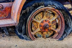 Rusted Out Wheel and Flat Tire. Poor rusted wheel sunk in the desert sand in the hot sun royalty free stock photos