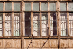 Poor rustic house with huge wooden windows frames in historical city Royalty Free Stock Photo