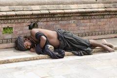 Poor sadhu, holy man sleeping on the street in Pashupatinath Temple, Kathmandu. Nepal. KATHMANDU, NEPAL - SEPTEMBER 29, 2016 : Poor sadhu, holy man sleeping on stock photo