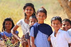 Poor school going kids near a village in Pune, India. Poor school going kids posing and smiling infront of the camera in a village near Pune, India royalty free stock images