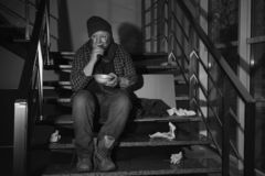 Poor senior man with bowl and bread on stairs. Black and white effect. Poor senior man with bowl and bread on stairs indoors. Black and white effect stock image