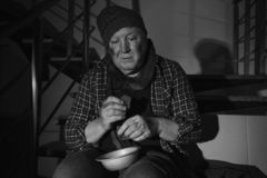Poor senior man with bowl and bread on stairs. Black and white effect. Poor senior man with bowl and bread on stairs indoors. Black and white effect royalty free stock photos