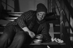 Poor senior man with bowl and bread on stairs indoors. Black and white. Effect royalty free stock image