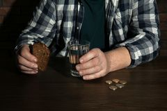 Poor senior man with bread and glass of water at table. Closeup stock photography
