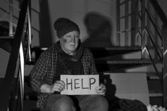 Poor senior man with cardboard sign HELP on stairs indoors. Black and white. Effect stock photography