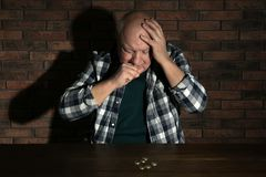 Poor senior man with coins at table. Near brick wall stock photo