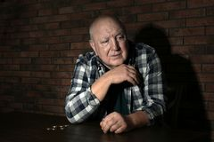 Poor senior man with coins at table near wall. Poor senior man with coins at table near brick wall stock images