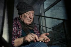 Poor senior man counting coins. On stairs indoors stock photography
