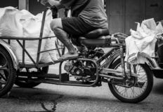 Poor senior man driving a motorbike, sending ice bag to a restaurant. Elderly people work after retirement. Retirement money. Crisis concept. Welfare government royalty free stock images