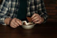 Poor senior man eating bread at table. Closeup stock image