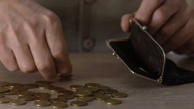 Poor senior man putting coins in wallet, social insecurity, low incomes, budget