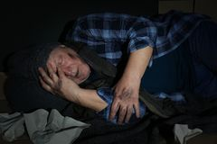 Poor senior man sleeping among garbage. On floor stock images