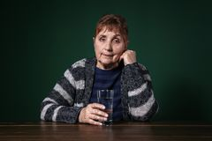 Poor senior woman with glass of water sitting at table. Against color background royalty free stock photos