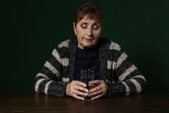 Poor senior woman with glass of water sitting at table. Against color background royalty free stock photo