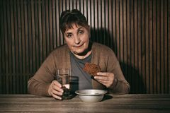 Poor senior woman with water and bread at table. Against wooden wall stock photography