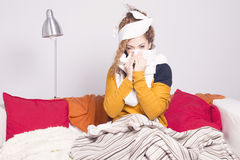 Poor sick woman, blowing her nose. Poor sick woman, blowing her nose sitting on the sofa Royalty Free Stock Image