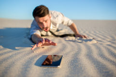 Poor signal. businessman searching for mobile. Poor signal. Frustrated young businessman searching for mobile phone signal while lying on sand in desert stock photo